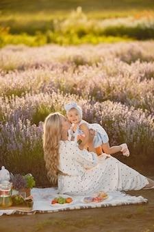 Moeder met dochtertje op lavendelveld. mooie vrouw en schattige baby spelen in weide veld. gezinsvakantie in zomerdag.