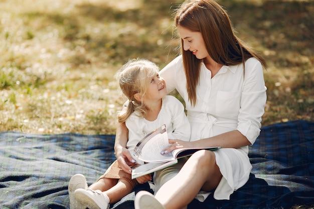 Moeder met dochtertje zittend op een plaid en lees het boek