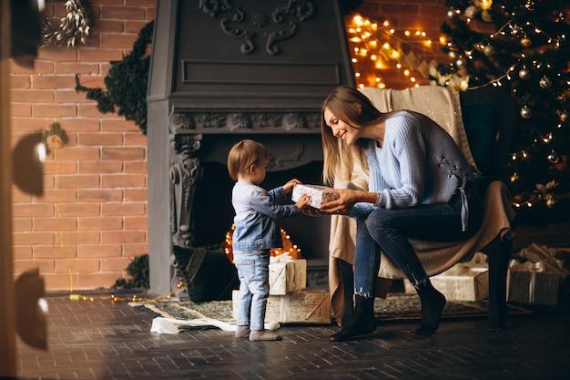 Moeder met dochterzitting als voorzitter door kerstboom