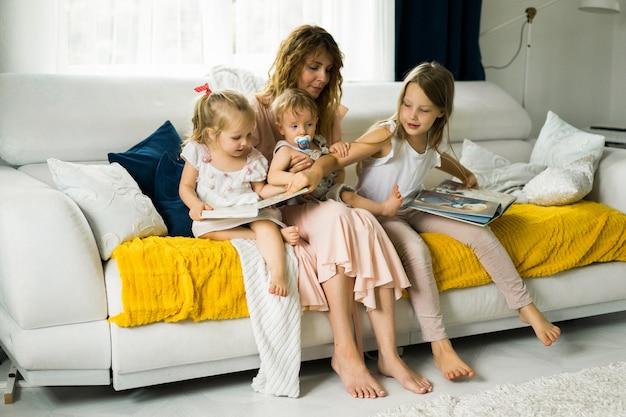 Moeder met drie kinderen die een boek lezen in een huiselijke sfeer