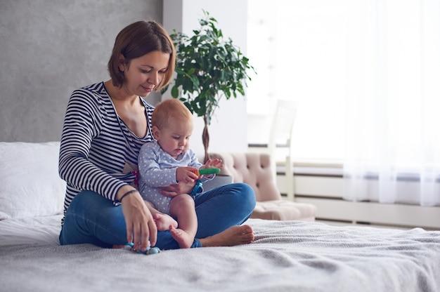 Moeder met een 8 maanden oude babyzitting op een bed thuis