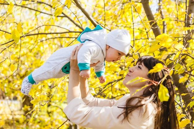 Moeder met een baby, een kleine jongen loopt in de herfst in het park of bos. gele bladeren, de schoonheid van de natuur. communicatie tussen een kind en een ouder.