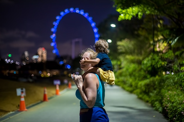 Moeder met een baby op haar schouders in het stadspark 's avonds tegen de achtergrond van het reuzenrad