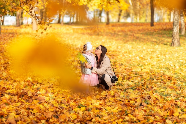 Moeder met een babydochter in stijlvolle kleding met een camerakus op de achtergrond van helder herfstgeel gebladerte in het park. familiewandeling en fotosessie over de gouden herfstnatuur