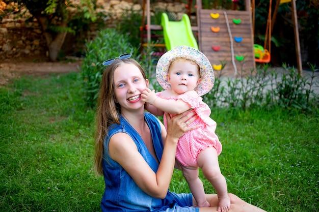 Moeder met een babymeisje op het groene gazon op de speelplaats in de zomer plezier