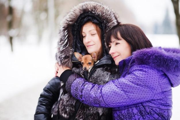 Moeder met een dochter en hun hond wandelen in winter park