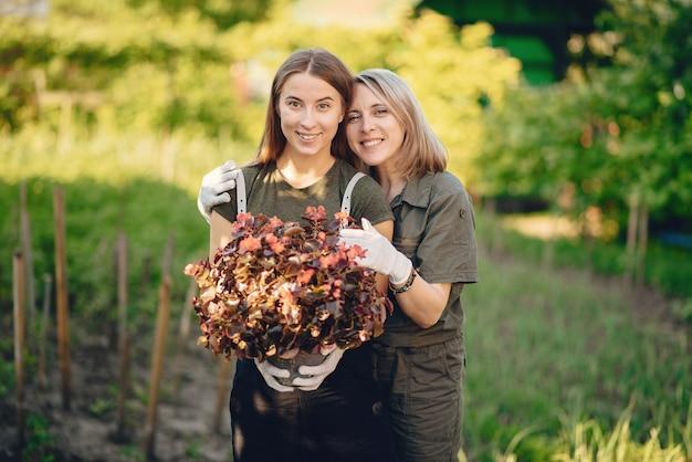 Moeder met een dochter werkt in een tuin in de buurt van het huis