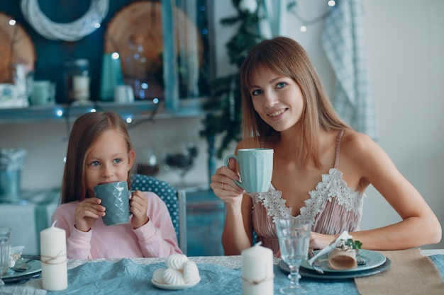 Moeder met een dochtertje zitten en ontbijten aan tafel in de keuken. blijf thuis.