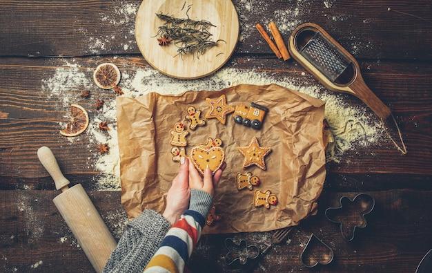 Moeder met een kind koken kerstkoekjes op een tafel
