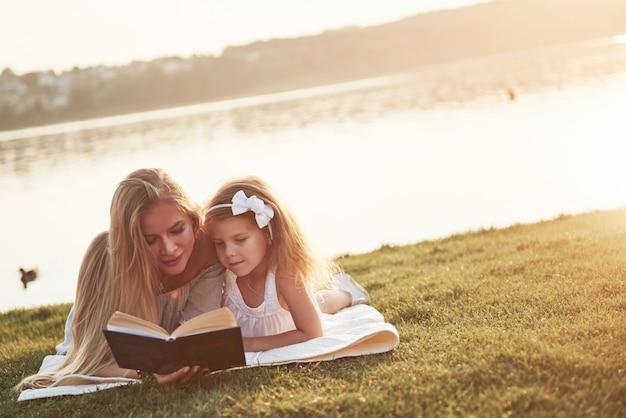 Moeder met een kind leest een boek op het gras