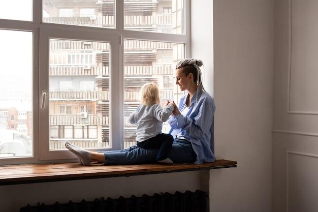 Moeder met een klein kind kijkt uit het raam