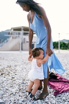 Moeder met een klein meisje staat hand in hand op het strand