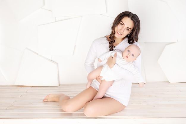 Moeder met een pasgeboren baby in haar armen thuis, het concept van een liefdevolle en gelukkige familie, moederdag