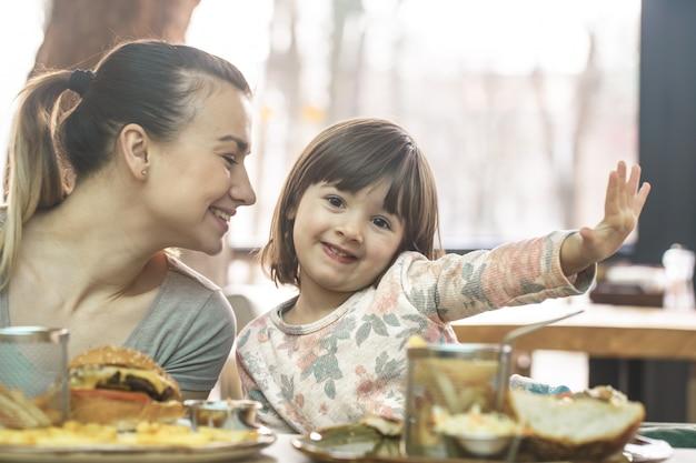 Moeder met een schattige dochter eten van fastfood in een café