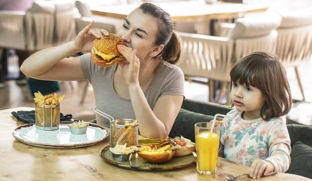 Moeder met een schattige dochter fastfood eten in een café