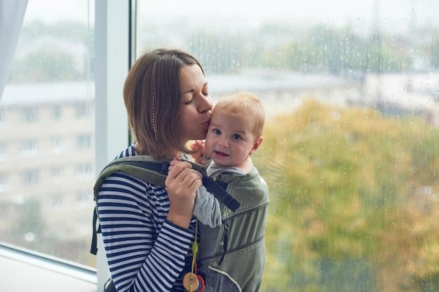 Moeder met ergobaby dragende peuter thuis.
