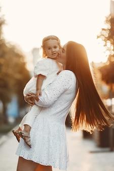 Moeder met gaughter spelen. vrouw in een witte jurk. familie op een zonsondergangachtergrond.