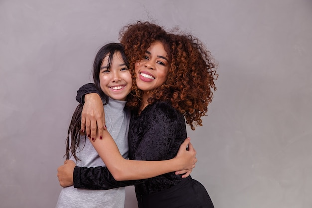 Moeder met geadopteerde dochter op grijze achtergrond. zwarte moeder met japanse dochter. adoptieconcept Premium Foto