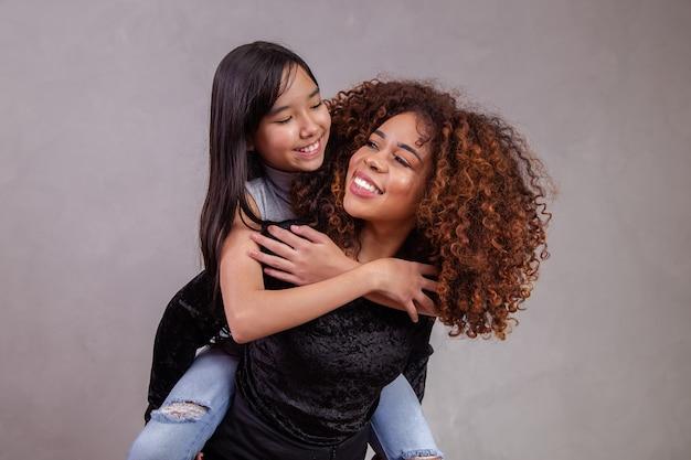 Moeder met geadopteerde dochter op grijze achtergrond. zwarte moeder met japanse dochter. adoptieconcept