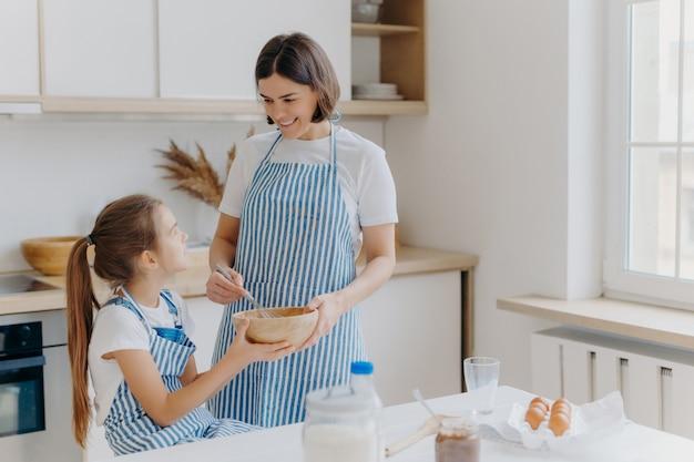Moeder met gelukkige glimlach, kookt samen met dochter in keuken