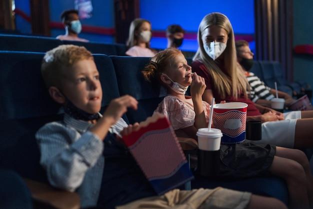 Moeder met gelukkige kleine kinderen die film kijken in de bioscoop, coronavirusconcept.
