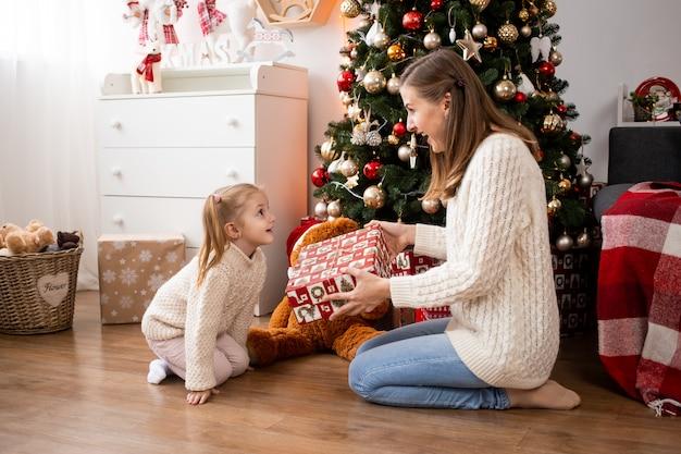 Moeder met geschenkdozen en haar kleine meisje