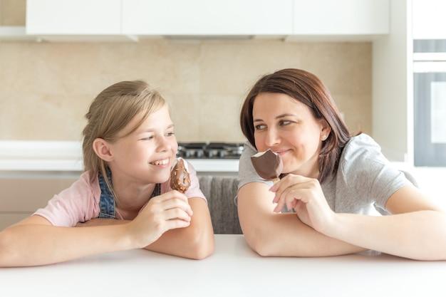 Moeder met haar 12-jarige dochter zit in de keuken eten van ijs, goede relaties van ouder en kind, gelukkige momenten samen