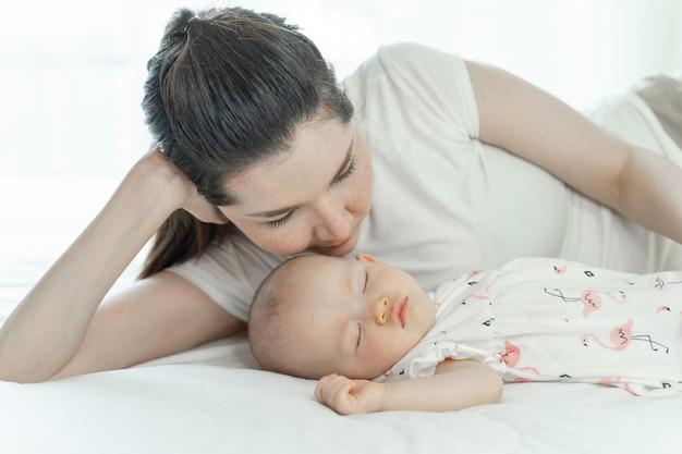 Moeder met haar babyslaap op slaapkamer