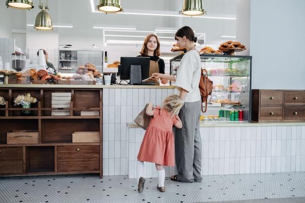 Moeder met haar dochter die voor gebak in een bakkerijwinkel betaalt. meisje is erg rusteloos en ongeduldig.