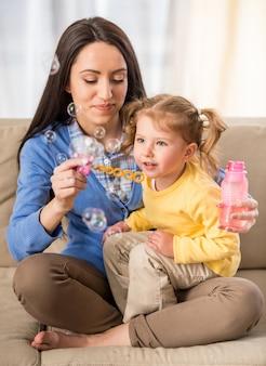 Moeder met haar dochter die zeepbels maakt.