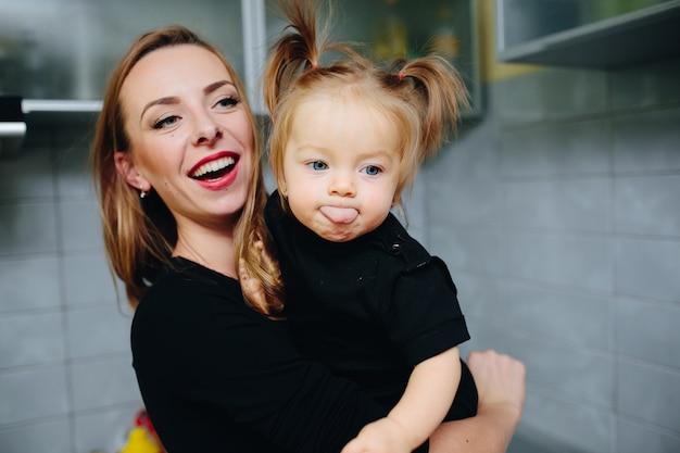 Moeder met haar dochter in de armen en het meisje met tong uit