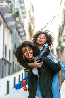 Moeder met haar dochter op de rug