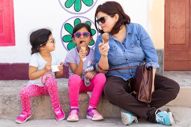 Moeder met haar dochters eten van ijs