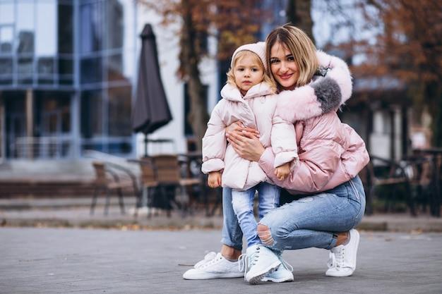 Moeder met haar dochtertje gekleed in warme doek buiten de straat