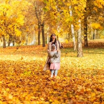 Moeder met haar dochtertje loopt in het herfstpark met gouden herfstbladeren
