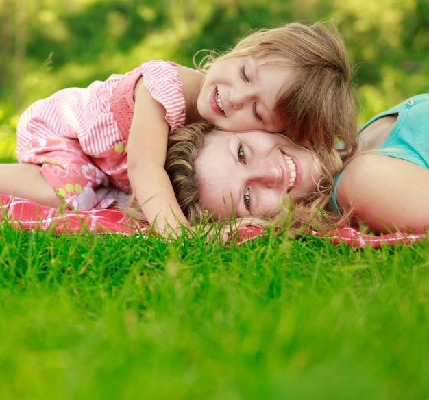 Moeder met haar gelukkige dochtertje liggen op het gras