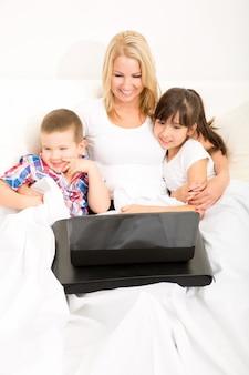 Moeder met haar kinderen met behulp van een laptop in bed