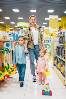 Moeder met haar kleine kinderen in kinderwinkel. moeder met dochter en zoon samen speelgoed kiezen in de supermarkt, familie winkelen