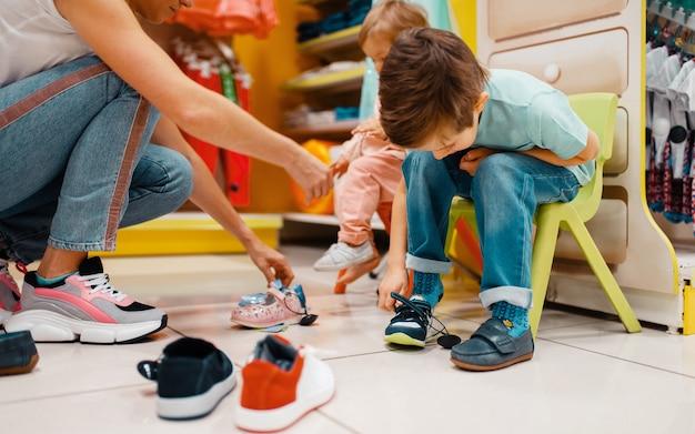 Moeder met haar kleine kinderen schoenen kiezen in kinderwinkel.