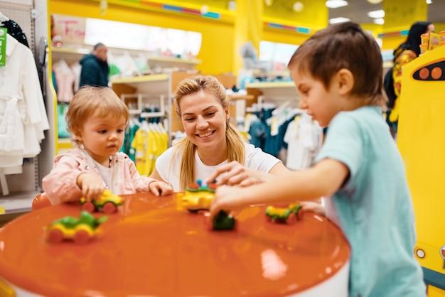 Moeder met haar kleine kinderen spelen in kinderwinkel.