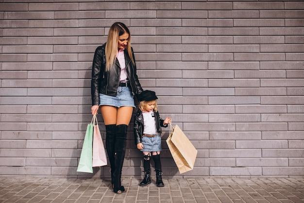 Moeder met haar kleine schattige dochter met boodschappentassen