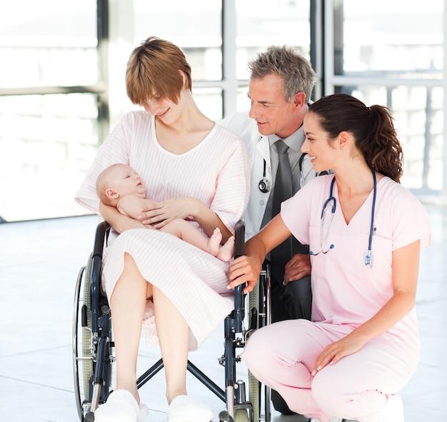 Moeder met haar pasgeboren baby, arts en verpleegkundige