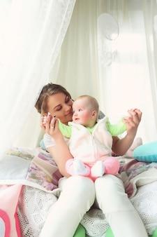 Moeder met haar pasgeboren handen van de babyzorg thuis