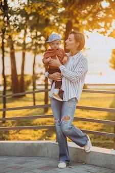 Moeder met haar peuterzoon in herfstpark