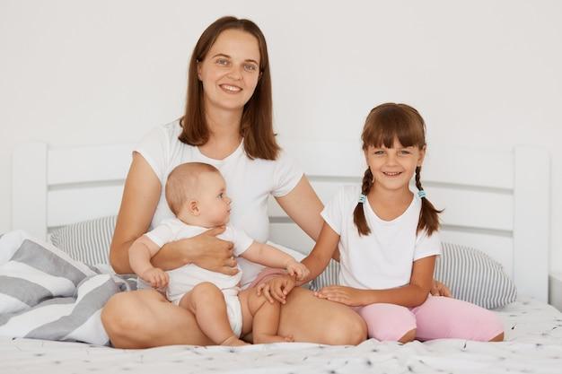 Moeder met haar schattige kleine dochters zittend op bed, samen genieten in vrije tijd, camera kijken met gelukkige gezichtsuitdrukkingen, gelukkig moederschap, ouderschap.
