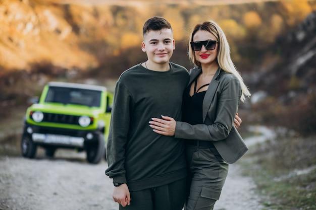Moeder met haar tienerzoon bij de auto