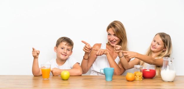 Moeder met haar twee kinderen aan het ontbijt wijzend naar de zijkant