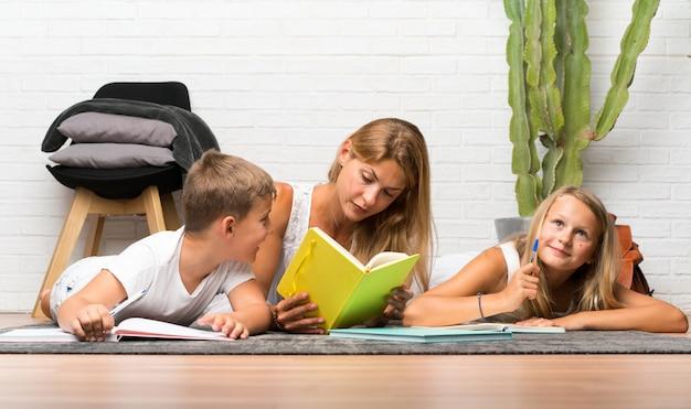 Moeder met haar twee kinderen binnenshuis en studeert