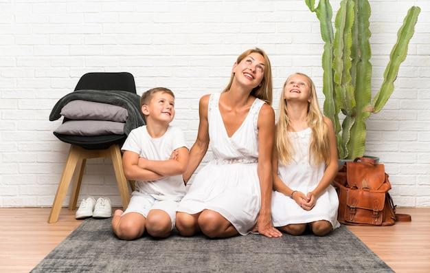 Moeder met haar twee kinderen die binnenshuis omhoog kijken
