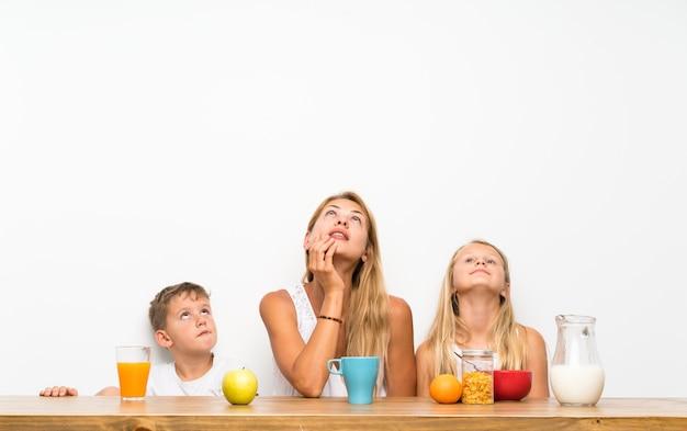 Moeder met haar twee kinderen die ontbijt hebben die omhoog eruit ziet